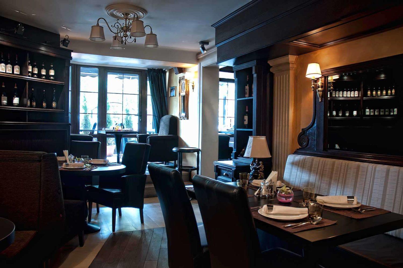 imagine din restaurant Il Calcio by Mr val, cu mobilier masiv de lemn, scaune mari, din piele, canapele capitonate, si o fereastra mare pe fundal