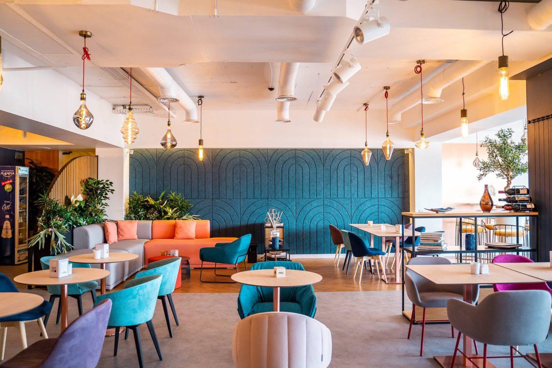 imagine de ansamblu din Sensio Living, cu mese de lemn si scaune colorate si un perete albastru, una din cafenele moderne