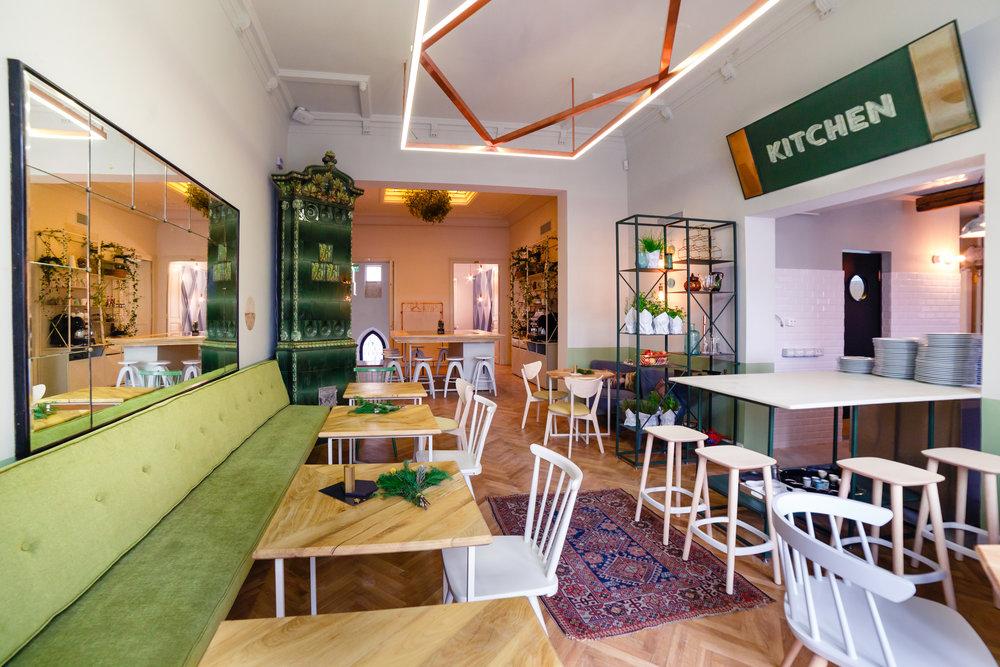 Una din incaperile de la simbio living din București, cu o canapea lunga, verde, oglinda mare, mese de lemn si scaune albe