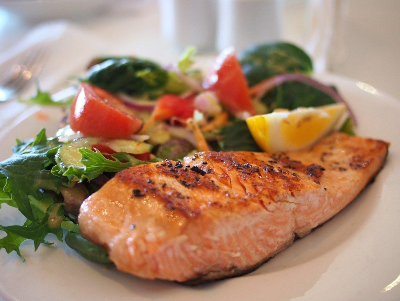 somon la cuptor, in farfurie alba, cu salata verde, rosii, lamaie, o combinatie care combate răceala și gripa