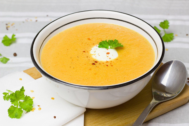 supa crema de legume cu verdeata si smantana, intr-un bol alb, metalic, cu o lingura langa el