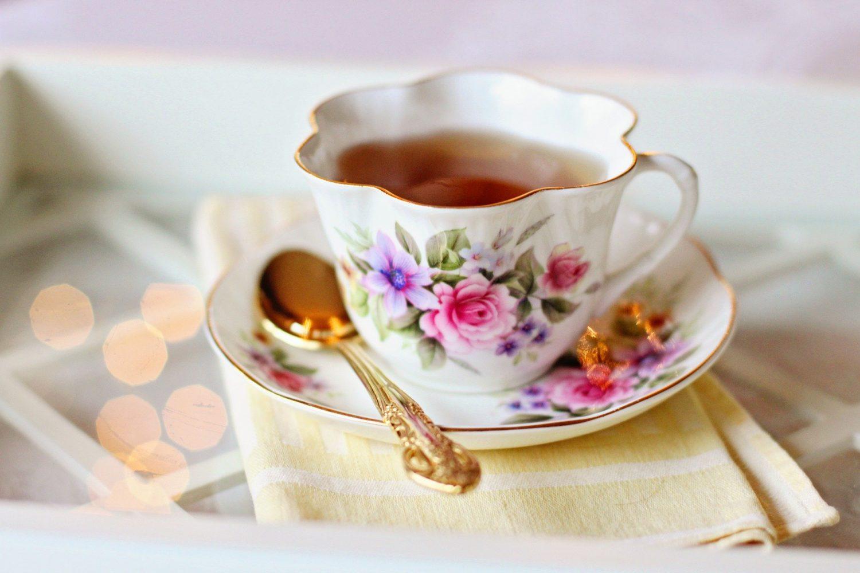 ceașcă albă de ceai din porțelan cu flori colorate, pictate si lingură aurie asezată pe farfurie