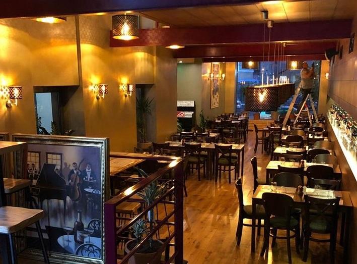 restaurant cu specific italian Trattoria Verdi Victoriei, cu imagine de ansamblu in care se vad multe mese de restaurant patrate si scuane de lemn, corpuri de iluminat atarnate si iluminat difuz