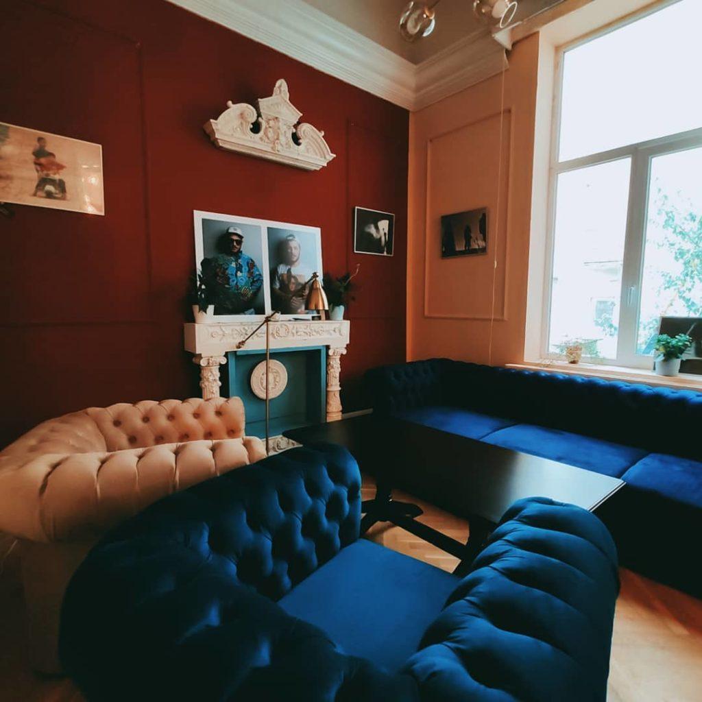 camera cu pereti visinii si ferestre mari, canapele masive albastre si albe, din victoria hub