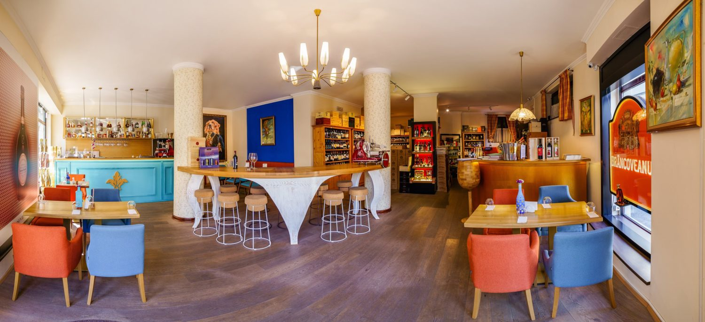 imagine de ansamblu din wine ambassador wine bars din bucurești, cu mese patrate si fotolii albastre si portocalii de o parte si alta, o masa inalta, circulara cu scaune inalte, rotunde, un peretre albastru cu pictura, doua coloane rotunde, ornamentale, un bar albastru in fundal si multe sticle de vin
