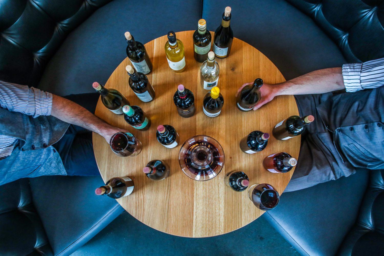 masa rotunda fotografiata de sus, pe fundal albastru, plina cu sticle de vin si doi oameni carora li se vad mainile servind un pahar de vin