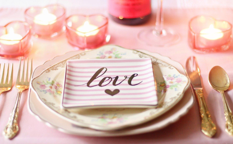 masa asezata frumos pentru Valentine's Day, cu farfurii de portelan suprapuse, pe prima este scris love, cu negru, cu tacamuri aurii asezate de o parte si de alta, lumanari in suport de sticla, in forma de inima, totul pe fundal roz si in nuante de roz, ca idee de marjeting pentru Valentine's Day