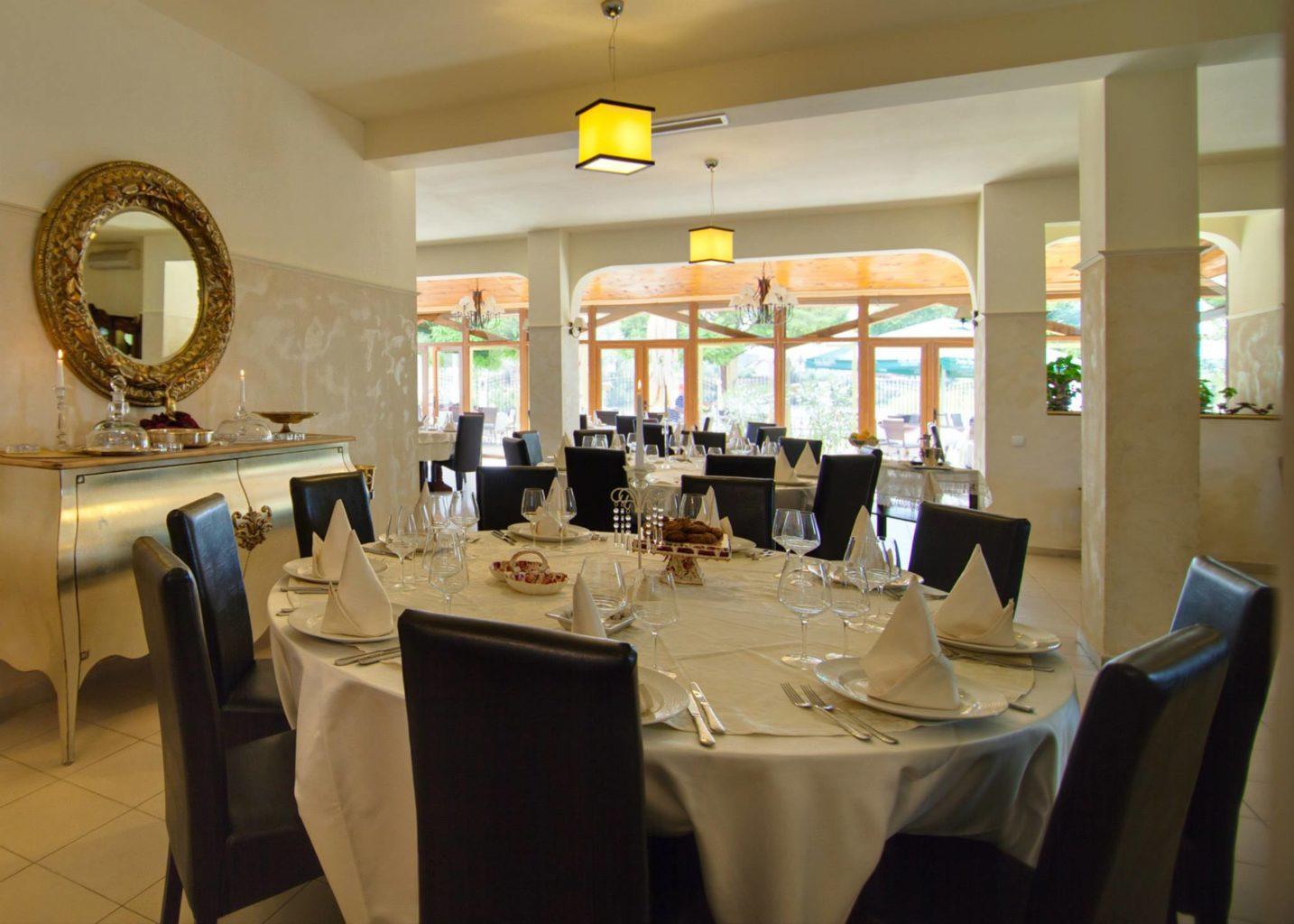 imagine din amvrosia restaurant cu specific grecesc, cu o masa mare rotunda cu fata de masa alba, scaune tapitate albastre, o oglinda aurie in stanga, pe perete si in fundal alte mese si un perete din sticla, catre terasa