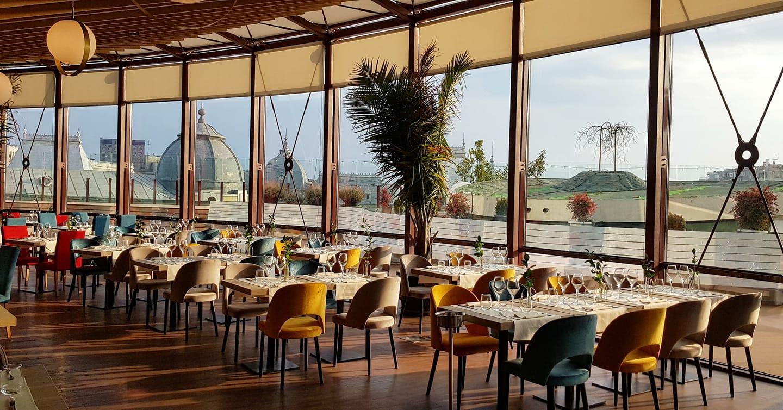 fotografie din restaurant aria tnb, cu un salon de mese semicircular, cu ferestre mari de sus pana jos si vedere catre terasa, doua randuri de scaune de cate 4 persoane si scaune tapitate in albastru, galben si crem, si plante decorative exotice, unul din restaurante de 8 martie la care sa iesi
