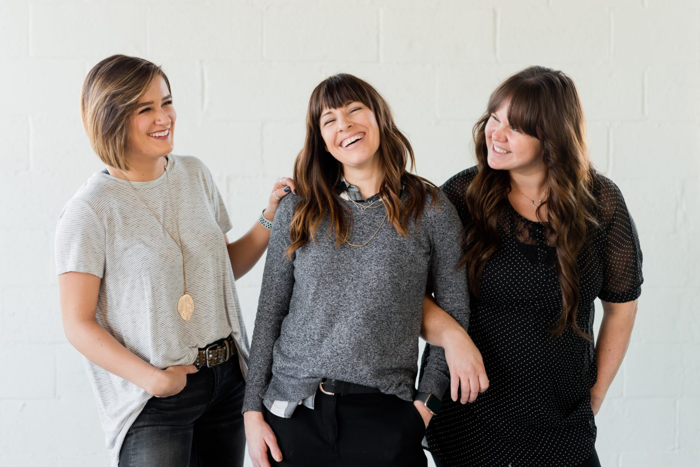 3 femei fotografiate pe fundal gri, stand in picioare si razand relaxate, imagine reprezentativa pentru prietene care ies la restaurant de 8 martie