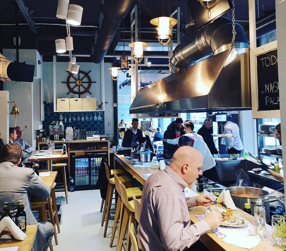 imagine de ansamblu din restaurant BistrMar, cu o masa lunga si inalta, din lemn deschis la culoare, cu scaune inalte din lemn, hota din inox suspendata deasupra, corpuri de iluminat suspendate de tavan, un barbat in prim plan, care mananca si mai multe persoane in fundal. Un restaurant cu aspect industrial și unul din restaurante pescărești din București