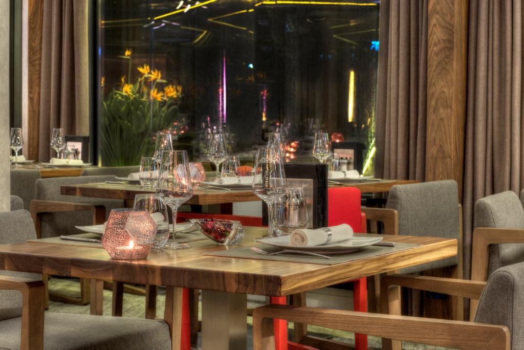 imagine detaliu din restaurant casa di david, cu mese de restaurant din lemn si scaune tapitate gri, iar pe masa sunt asezate pahare de vin de cristal, lumanari si farfurii albe, acesta fiind unul din restaurantele unde sa mergi la prima intalnire