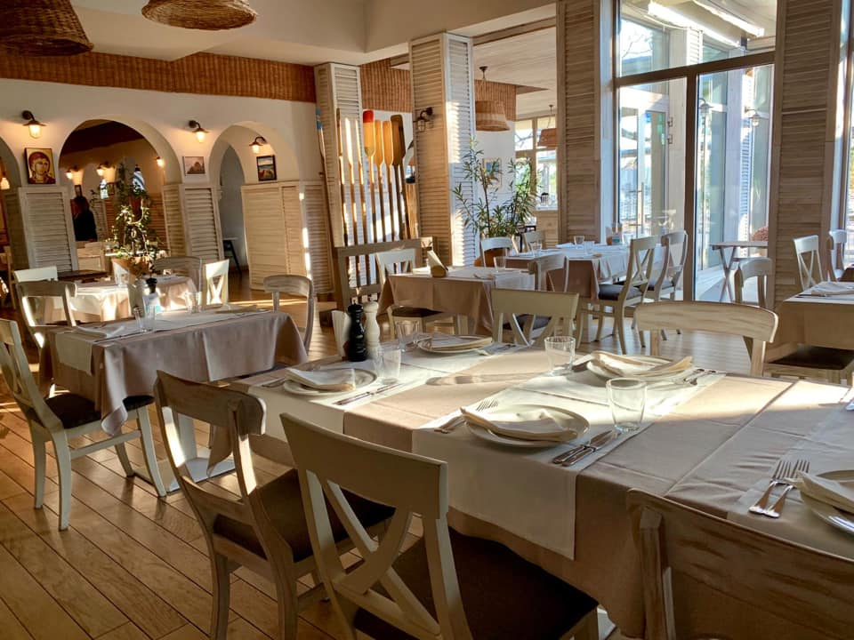 imagine de ansamblu din cherhanaua ancora, cu o masa mare in prim plan, cu fata de masa alba, tacamuri si farfurii asezate, mobilierul este din lemn deschis la culoare, peretii sunt albi. Unul din restaurante pescărești din București