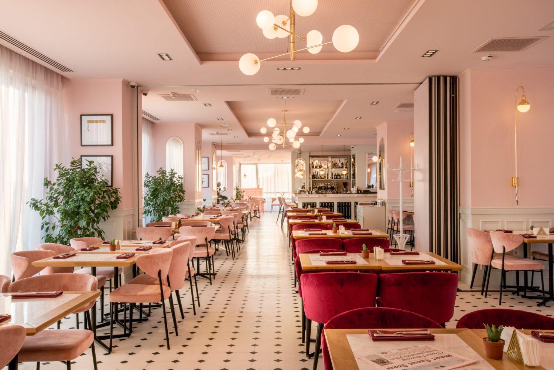 imagine de ansamblu din cismigiu bistro la etaj, in care se vede tot restaurantul, cu un rand de scaune pe stanga, cu scaune roz, alt rand de mese in dreapta, cu scaune visinii din catifea, pereti roz, corpuri de iluminat suspendate si podea mozaic, in alb si negru