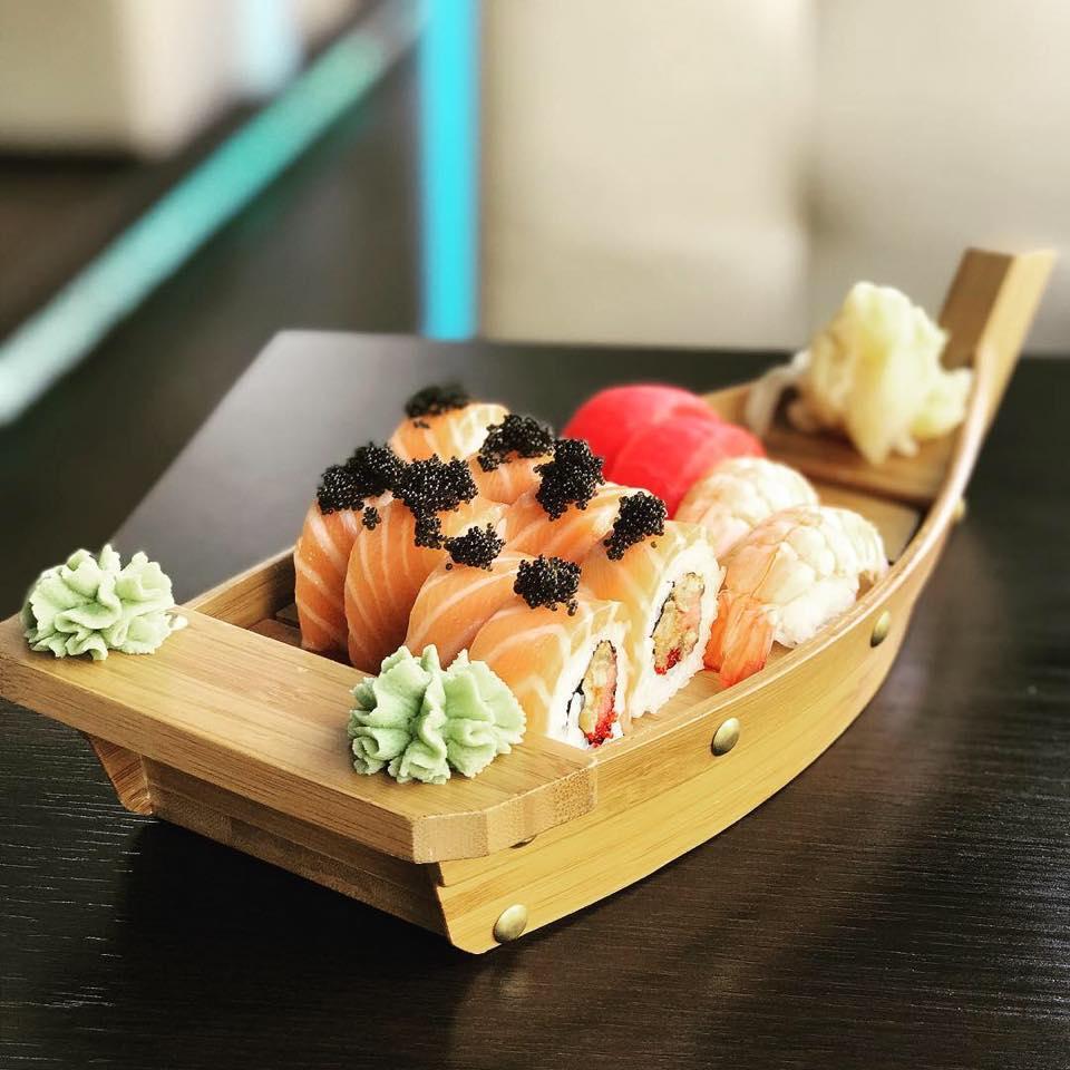 Close up cu un platou corabie de la Sushi Terra, corabie din lemn plina cu role de sushi din peste si orez, unul din cel mai bun sushi București