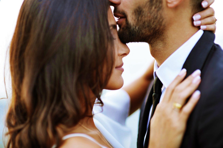 prim plan cu un cuplu de indragostitit, un barbat imbracat la costum negru, care saruta pe cap o femeie bruneta cu parul lung, de Ziua Indragostitilor