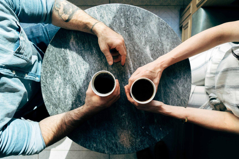 masa rotunda, gri, fotografiata de sus, la care sta unbarbat si o femeie carora li se vad doar mainile, fiecare tinand in mana o ceasca de cafea, imagine sugestiva pentru un cuplu de indragostiti aflati la prima intalnire la un restaurant