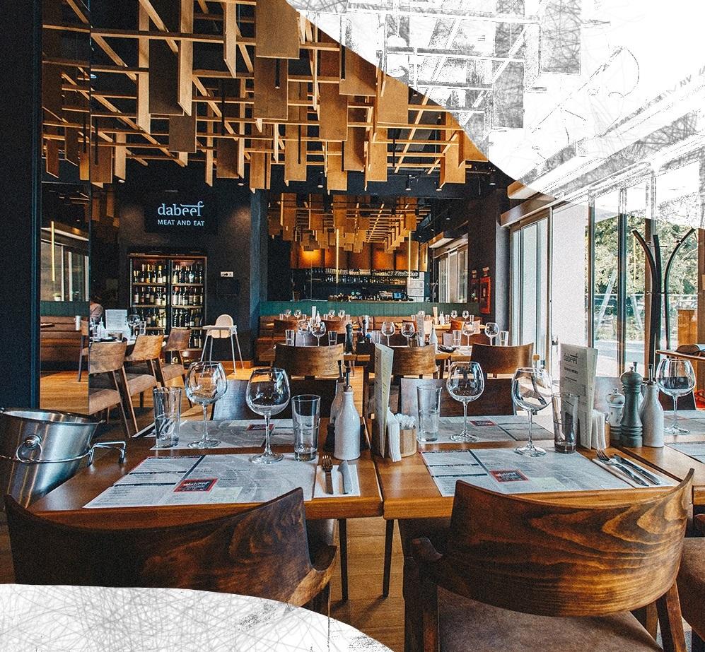 doua randuri de mese din restaurant DaBeef, mese si scaune din lemn lacuit, cu stergare si pahare asezate pe masa, ferestre mari in dreapta, si un tavan decorat cu bucati de lemn, peretii sunt negri