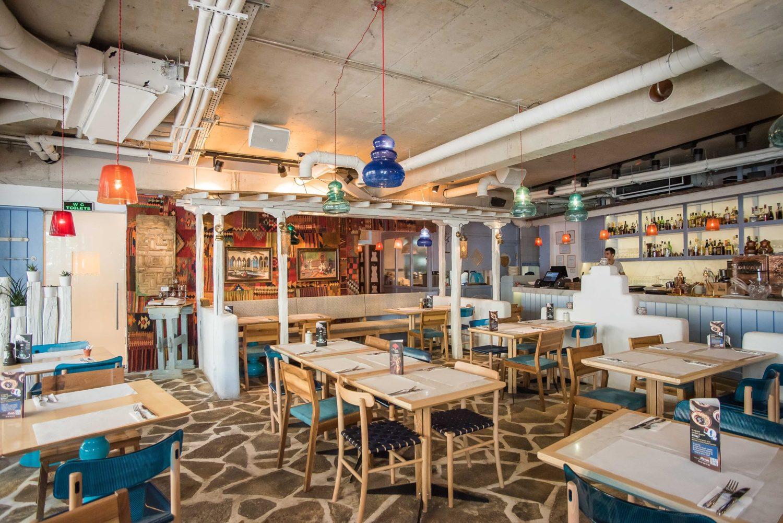 imagine de ansamblu din restaurantul Divan, amenajat in stil oriental, cu podea pietruita, tavan din beton, mese din lemn deschis la culoare si scaune tapitate cu albastru, o canapea lunga in dreptul unor coloane orientale, iar pe un perete un covor decorativ, unul din restaurante perfecte pentru 1 Martie