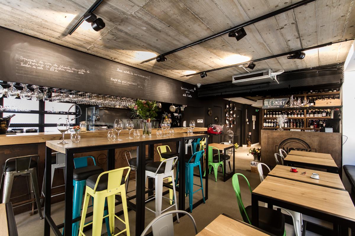 imagine din enotek wine bar, cu mese patrate din lemn, scaune colorate, o masa inalta de bar, cu blat de lemn si picioare din fier, cu scaune de bar colorate, si in fundal un perete cu raturi luminate, cu sticle de vin