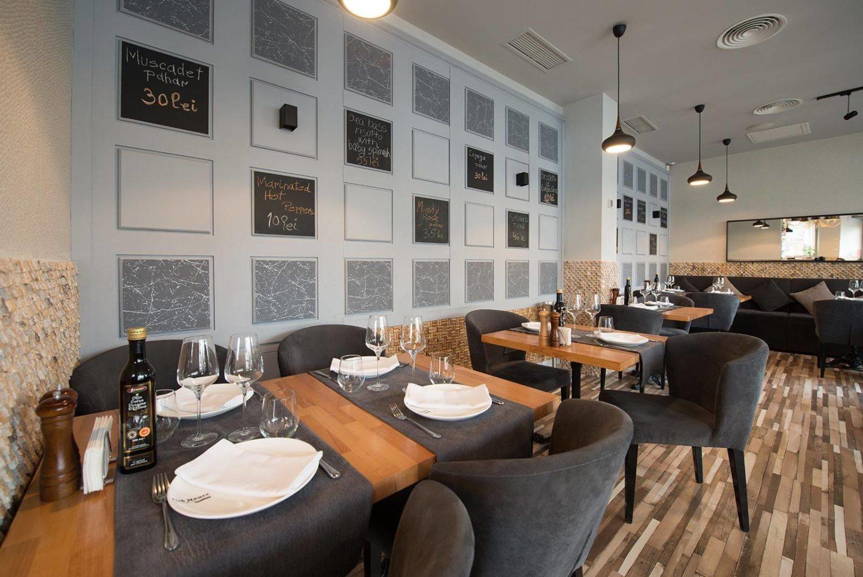 imagine cu doua mese din restaurantul fish house, mese de lemn cu stergare gri si farfurii albe, scaune gri inchis, tapitate, un perete alb cu multe rame de fotofraii si podea de lemn, unul din restaurante pescărești București