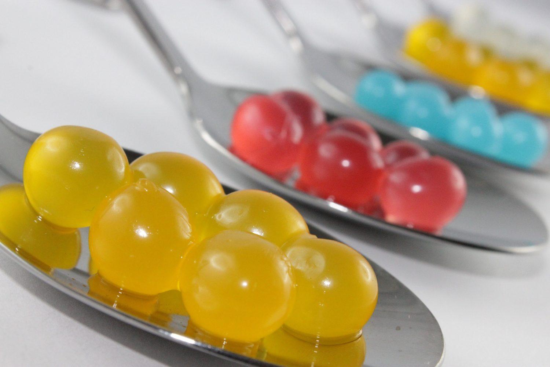 prim plan cu lingurite metalice, fiecare avand bobite colorate, galbene, rosii si albastre, reprezentative pentru procedul de sferificare practicat in gastronomie moleculara