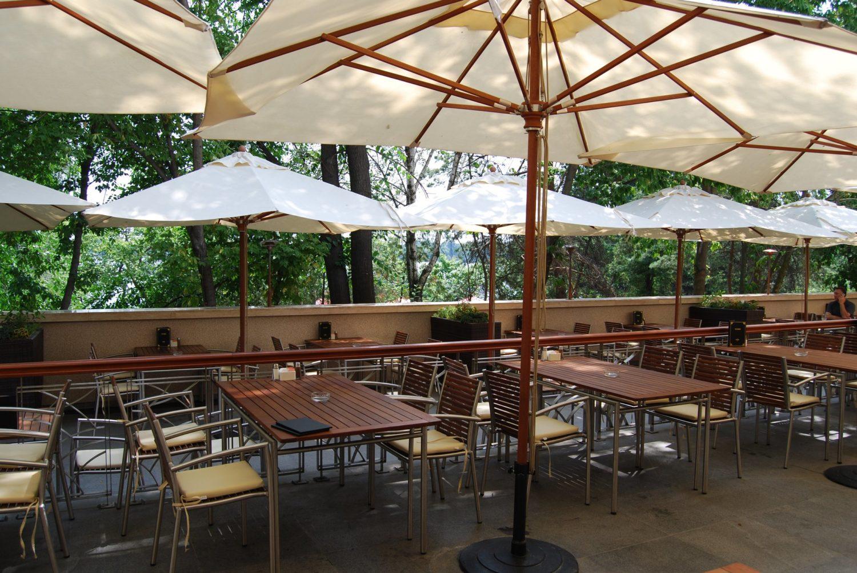 imagine cu terasa de la Hard Rock Cafe Bucharest, cu mese de lemn si umbrele albe, si cu o priveliste catre verdeata din parcul Herastrau, unul din restaurante perfecte pentru 1 Martie