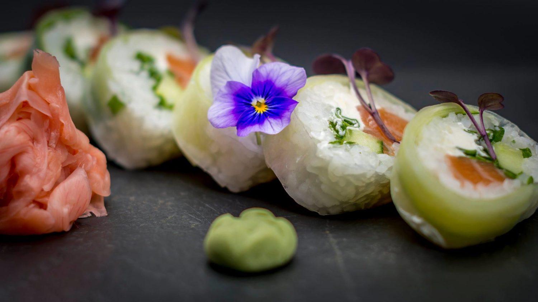 closeup cu 5 bucati de sushi de la Kanpai Bistro, cu role din orez si peste crud si un strop de wasabi langa, fotografiate pe fundal negru, cu o floare mica albastra decorativa