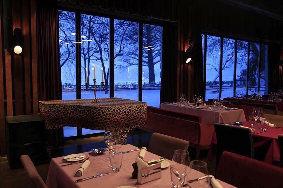 imagine din la brasserie bistro&lounge, unul din restaurante romantice din bucuresti, fotografie facuta pe inserat, cu lumina difuza, in care se vad in prim plan mese patrate cu fete de masa roz, si canapele visinii, un pian cu imprimeu leopard si pereti mari din sticla prin care se vede terasa imbracata in zapada