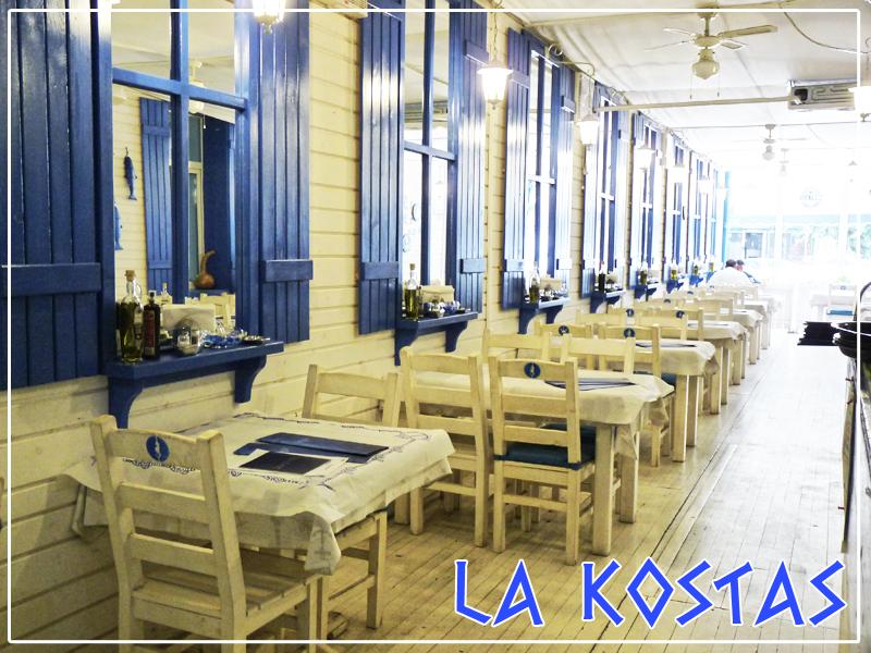 restaurant la kostas taverna, unul din restaurante cu specific grecesc in bucurești, cu mese albe de 6 persoane, cu scaune albe, podea alba si un perete alb, cu ferestre decorative, cu obloane albastre