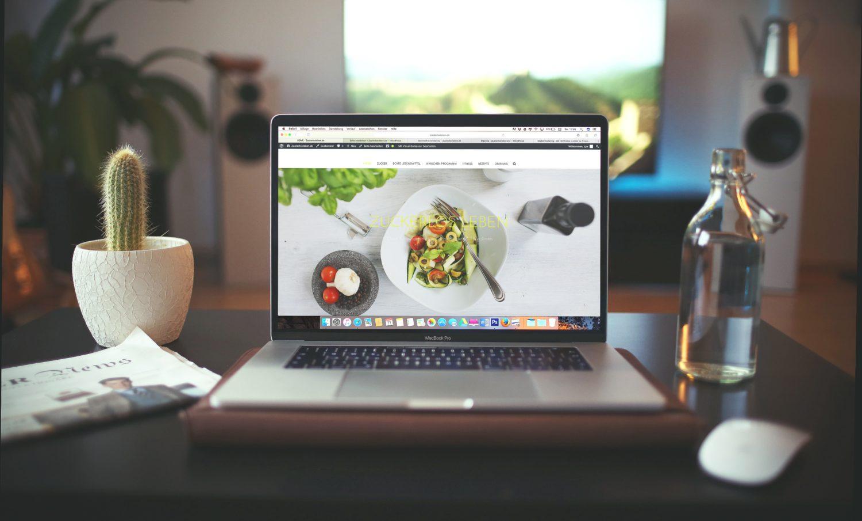 imagine cu un laptop deschis asezat pe un birou, iar pe monitor se vede pagina de website a unui restaurant, si in fundal o fereastra, iar langa laptop un ghiveci cu un cactus, imagine reprezentativă pentru cum descoperă oaspeții un restaurant
