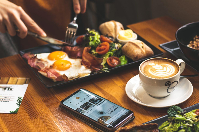 prim plan cu masa la restaurant, la care ia micul dejun o persoană căreia ii vedem doar mainile tinand tacamurile, cu un platou in fata cu oua ochiuri, paine, bacon si salata, langa care este asezata o ceasca de cafea si un telefon mobil, imagine reprezentativa pentru aplicația de rezervare la restaurante
