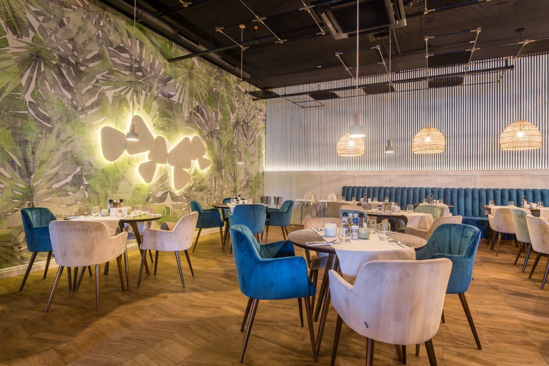restaurant monte fiore, cu un salon care are mese de patru persoane, cu scaune capitonate in culori de albastru si crem, podea de lemn, un perete cu tapet floral exotic si un corp de iluminat ambiental, cu forma nedefinita, si alte corpuri de iluminat rotunde, suspendate de tavan cu fire lungi, unul din restaurante de 8 Martie