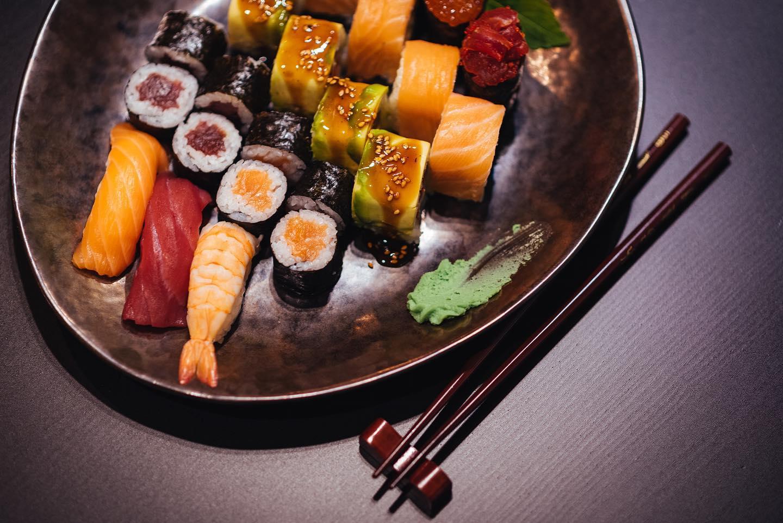 farfurie cu sushi de la restaurant nadasan, fotografiata pe fundal negru, o farfurie metalica cu sushi, role in mai multe variante, cu doua betisoare chinezesti asezate langa, unul din cel mai bun sushi București