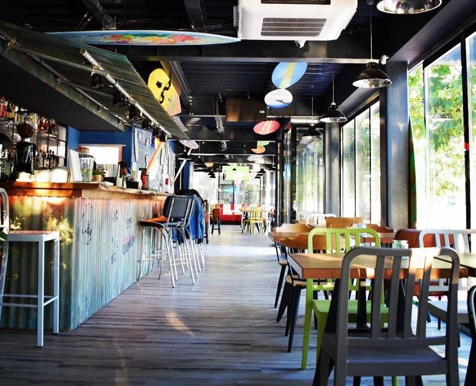 imagine de ansamblu din Kacked Kitchen & Beac Bar, cu barul lung, in stanga si cu scaune de bar, iar in dreapta un rand de mese asezate in dreptul unor ferestre mari, unul din restaurante perfecte pentru 1 Martie