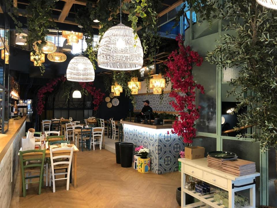 restaurant nikos greek taverna selari, unul din restaurante cu specific grecesc din bucurești, cu mese de patru persoane, un bar imbracat in gresie alba cu modele albastre, multe plante decorative si corpuri de iluminat suspendate aprinse