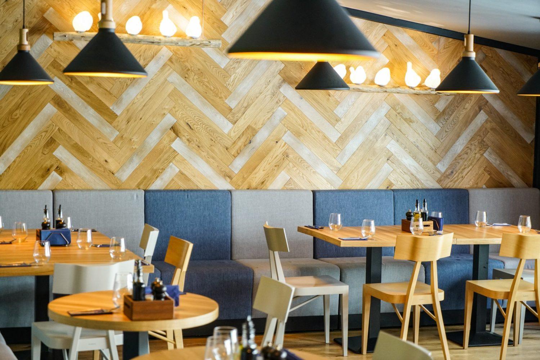 imagine din restaurant pio bistro, cu un perete din lemn asemanator parchetului, un sir lung, la perete, de canapea modulara in nuante de albastru si gri si mese cu scaune din lemn deschis la culoare in fata ei. Unul din restaurante perfecte pentru 1 Martie