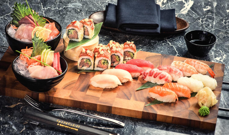 mix de sushi de la Ginger Sushi Bar & Lounge, cu mai multe tipuri d esushi pe un tocator de lemn, doua boluri negre cu peste si orez, servetele negre si tacamuri, totul fotografiat pe un fundal negru marmorat