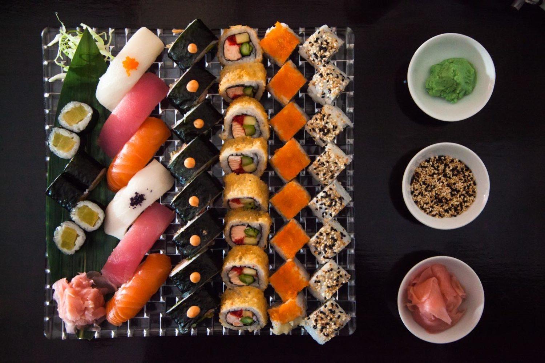 platou patrat cu multe sortimente de la restaurant Sushi Garden, cu sushi si role, nigri si maki, cu trei boluri rotunde asezate in dreapta, toate pe fundal negru