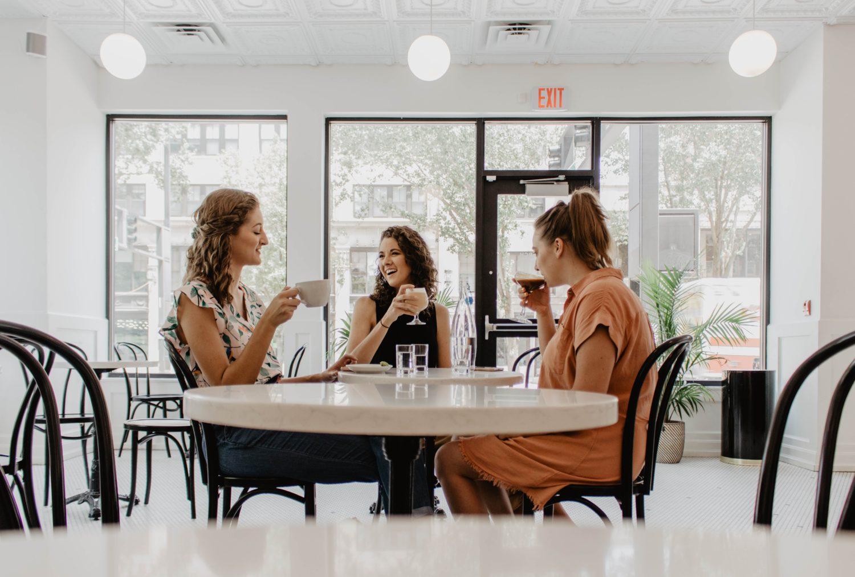 3 femei band o cafea la o masa rotunda intr-un restaurant decorat cu mult alb si ferestre mari in spate