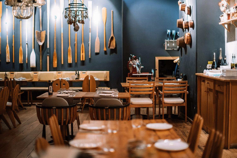 imagine din restaurant sardin, cu o masa patrata, din lemn, in prim plan, pe care sunt asezate farfurii si pahare, si alte doua mese patrate, din lemn, in fundal, cu saune de restaurant. In spate este un perete albastru, pe care stau atarnate obiecte decorative din lemn, asemanatoare cu niste linguri imense
