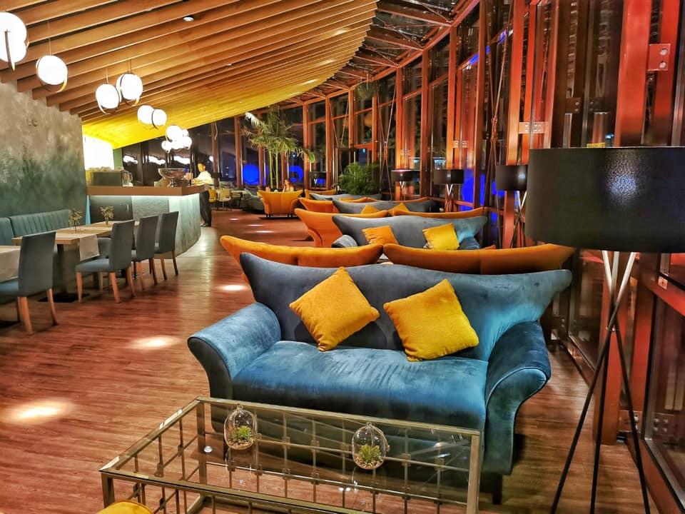 privire de ansamblu din restaurant artia tnb, cu un rand de canapele mari, din catifea, coloarate, albastre si galbene, cu perne galbene, si mese din sticla intre ele, un alt rand de mese patrate, de restaurant in partea stanga, si ferestre mari, panoramice, in dreapta. Restaruantul este fotografiat seara, si iluminat discret, fiind unul din restaurantele unde sa mergi la prima intalnire