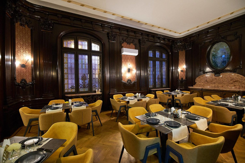 incapere din restaurantul ciao niki, unul din restaurante romantice din bucuresti, cu pereti imbracati in lambriuri din lemn inchis la culoare, ferestre mari, rotunjite, vitrate, si mese patrate, de cate 6 persoane, cu scaune galbene imbracate in catifea