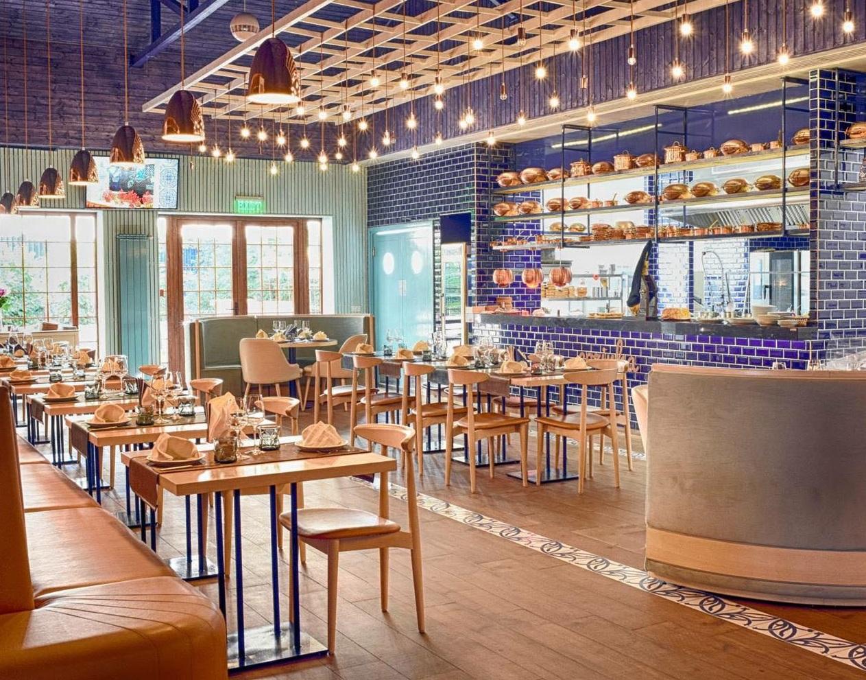 imagine din restaurant dancing lobster, cu un perete din faianta albastra, podea de lemn, rafturi decorative cu vase de gatit din alama, si mese de patru persoane cu scaune din lemn, dar si o canapea lunga, din piele portocalie, o idee de restaurant de 8 martie