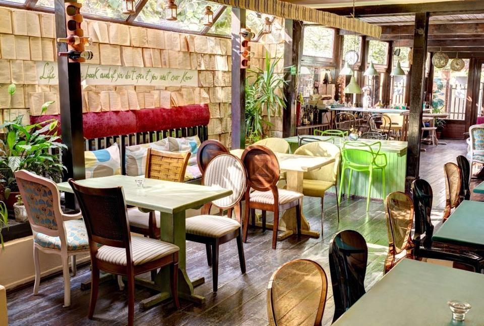 imagine din restaurant erra, cu mese de patru persoane la care sunt asezate scaune cu un design clasic, de jur impresur sunt pereti din sticla si un perete in stanga format din carti deschise