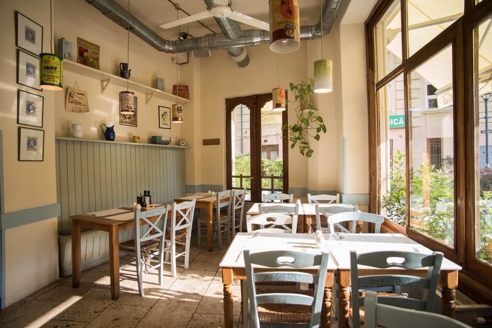 fotografie in restaurant meze taverna, restaurante cu specific grecesc, cu mese de patru persoane si scaune din lemn, fete de masa alba, pereti albi si bleo, ferestre mari, din lemn, in dreapta si accente decorative pe pereti