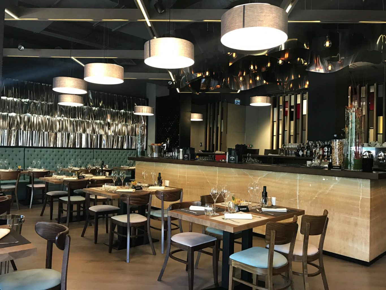 mozzafiato, unul din restaurante romantice din bucurești, cu mese patrate si patru scaune, din lemn, asezate in linie cu un bar auriu, iar pe fundal se vede un perete argintiu, si un rand de canapele capitoate, iar de tavan sunt prinse patru corpuri moderne de iluminat, rotunde