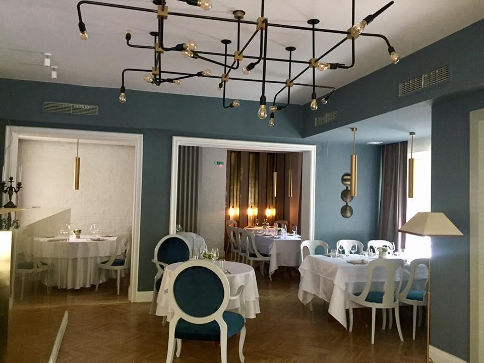 imagine de ansambu din pata negra, unul din restaurante romantice din bucuresti, o incapere cu pereti gri, tavan alb, podea de lemn, mese albe si scaune cu spatare rotunde, gri, iar de tavan este prinsa o instalatie de iluminat cu multe bare metalice
