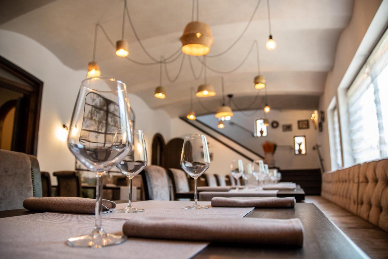 imagine de detaliu din restaurant rost, cu un sir de mese in prim plan, pe care sunt asezate pahare de cristal se stergare, iar pe fundal se vede un candelabru mare, cu mai multe brate si o scara spre etaj, unul din restaurantele unde sa mergi la prima intalnire