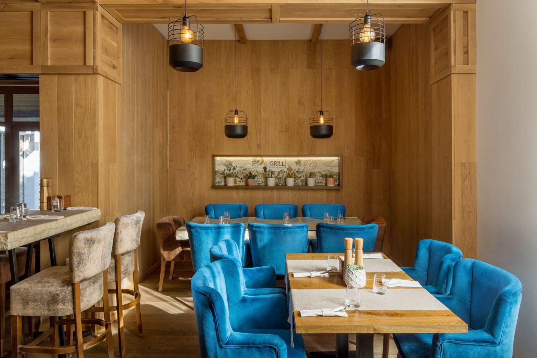fotografie din restaurant the grill, cu mese  din lemn si scaune tapitate din catifea albastra, cu peretii imbracati in lemn, un tablou si corpuri de iluminat suspendate de tavan, unul din restaurante de 8 martie